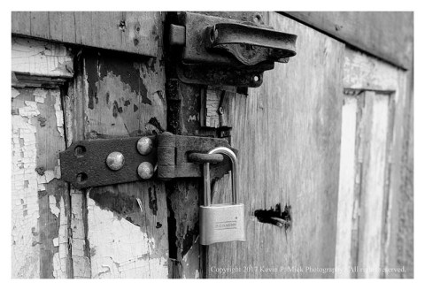 BW photograph of a rusted hasp and padlock on worn doors.
