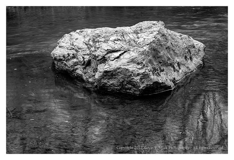 BW photograph of a single boulder mid-stream.