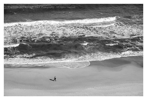 BW photograph of a lone walker on the beach at Ocean City, MD.