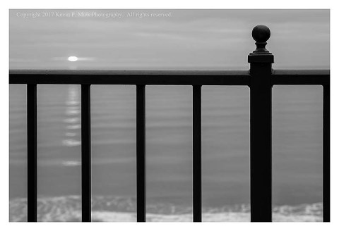 BW photograph of a sunrise over the Atlantic Ocean from a balcony.