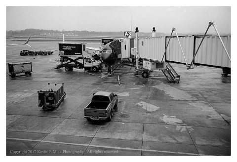BW photograph of a plane in a terminal.