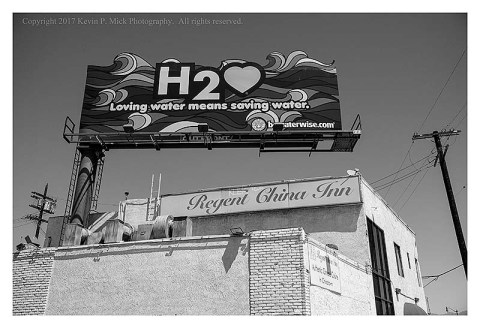 "BW photograph of a billboard in Los Angeles saying ""Loving Water Means Saving Water""."