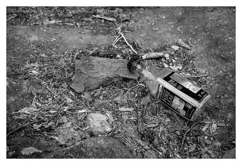 BW photograph of a discarded tea bottle laying on a the ground in the woods.