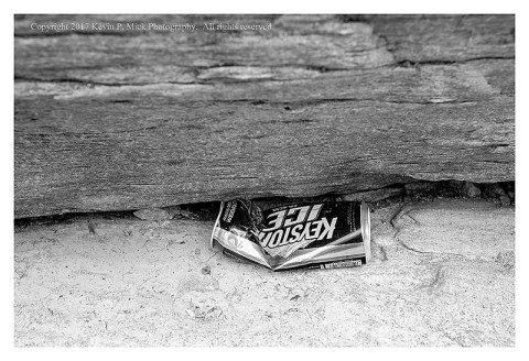 BW photograph of a folded beer can wedged under a rock.