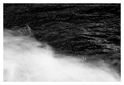 BW photograph of a wet black rock with white water moving past.