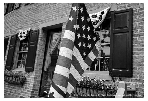BW photograph of a United States flag hanging outside a shop for Memorial Day.
