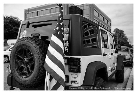 BW photograph of a United States flag attached to a Jeep.
