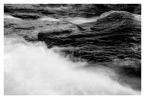 BW photograph of blurred water running among dark rocks.