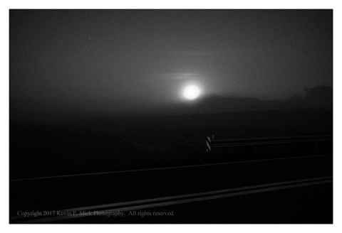 BW photograph of a moonset across a road.