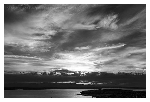 BW photograph of the sun setting behind the Olympic Mountain Range-third in a series.