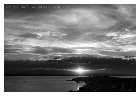 BW photograph of the sun setting behind the Olympic Mountain Range-fourth in a series.