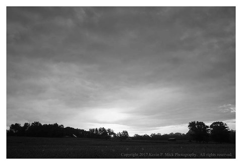 BW photograph of a sunrise over a field.