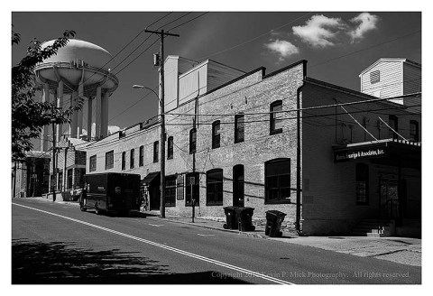 BW photograph of buildings and a water tower.