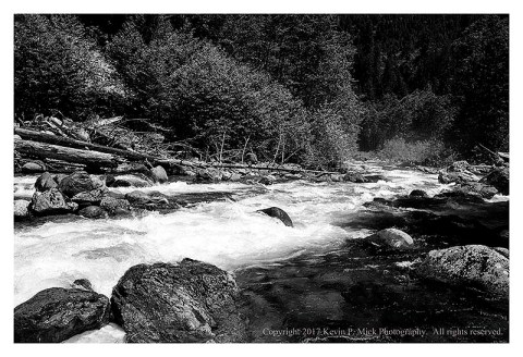 BW photograph looking downstream at water running next to the Mountain Highway.