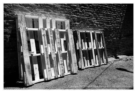 BW photograph of palettes against a brick wall.