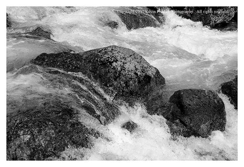 BW photograph of running water amid rocks next to the Mountain Highway.