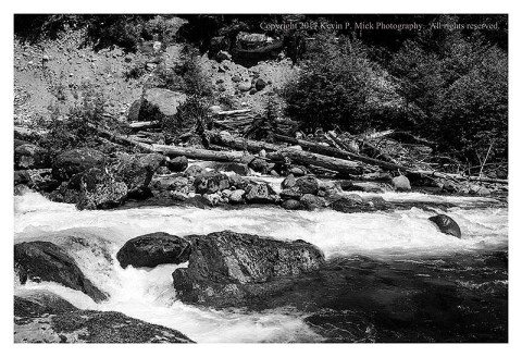 BW photograph looking across the running water at a debris pile next to the Mountain Highway.
