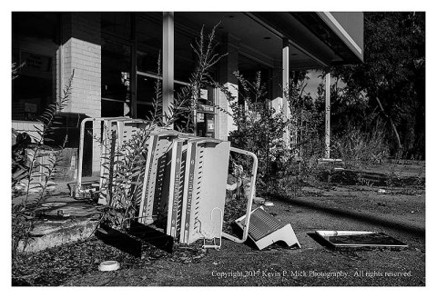 BW photograph of an upturned cigarello rack outside of an abandoned gas station.