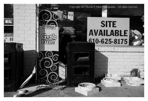 "BW photograph of the ""Site Available"" sign in the abandoned gas station."