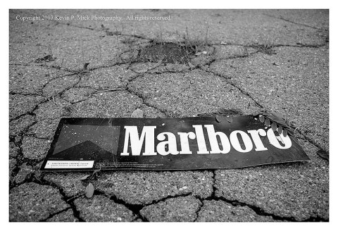 BW photograph of a Marlboro sign laying in a parking lot.