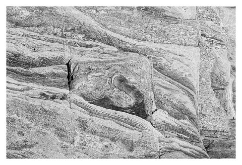 BW photograph of striated rock.