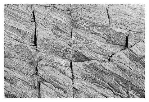 BW photograph of striated rock with vertical cracks.