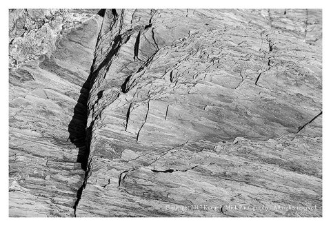 BW photograph of striated rock with one vertical crack.