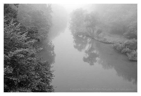 BW photograph of a foggy river.