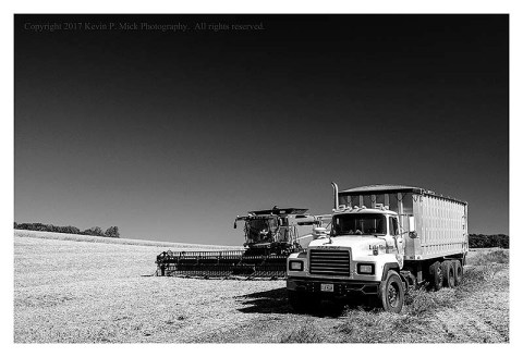 BW photograph of a truck and combine in a harvested field.