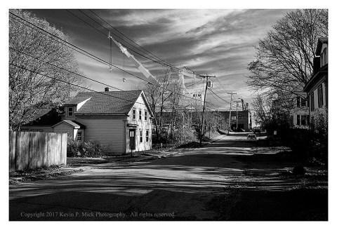 BW photograph of the neighborhood nearby, and the crane, at Bath Iron Works in Bath. ME.