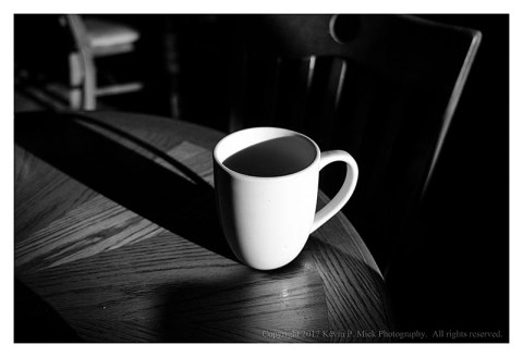 BW photograph of a strongly-lit coffee cup.