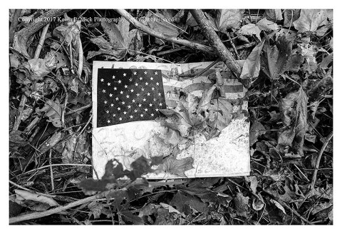 BW photograph of a United States flag facsimile laying among leaves and sticks.