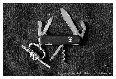 BW photograph of a Wenger Swiss Army Knife with the implements displayed.