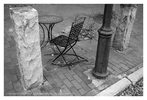 BW photograph of a table and chair on the sidewalk in Bath, ME.