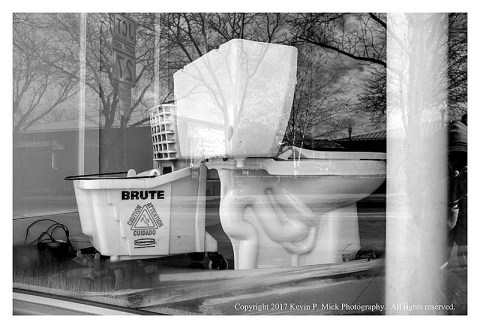 BW photograph of a toilet sitting in a store window.