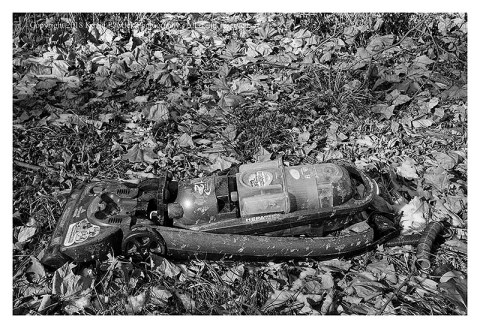 BW photograph of a Bissell vacuum cleaner laying in the leaves-side view.