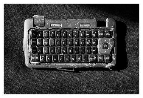 BW photograph of a trashed keypad from a flip phone.