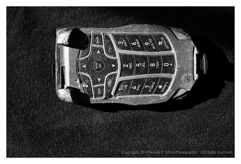 BW photograph of a trashed flip phone.