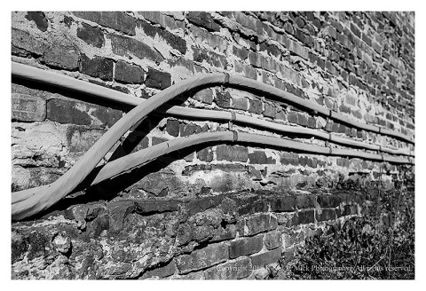 BW photograph of cables running along a brick wall.