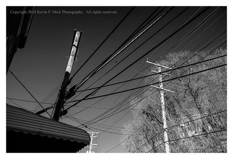 BW photograph of telephone poles and wires.