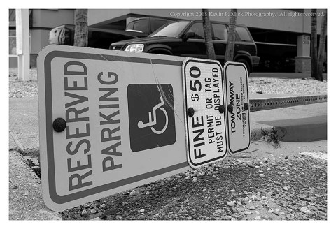 "BW photograph of a downed ""Reserved Parking"" sign in Ocean City."