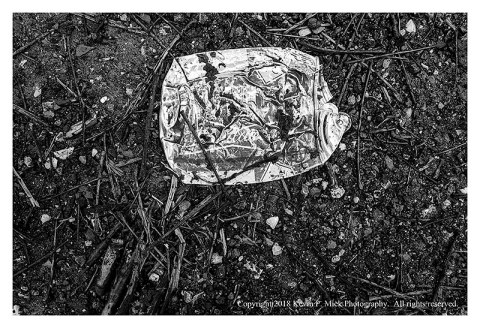 Bw photograph of a crushed Coca Cola can laying beside a road.