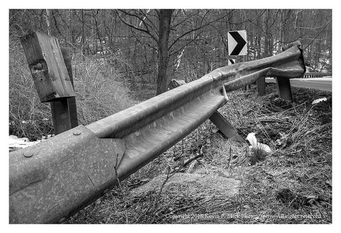BW photograph of a damaged guardrail after a crash.