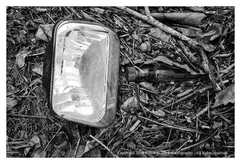 BW photograph of a broken headlight and bottle amid leaves beside a road.