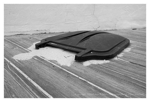 BW photograph of a blown off lid and sand on the boardwalk in Ocean City.