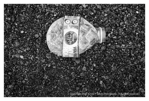 BW photograph of a crushed Nestle water bottle in a parking lot.