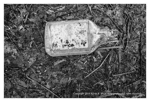 BW photograph of a crushed plastic bottle beside a road.