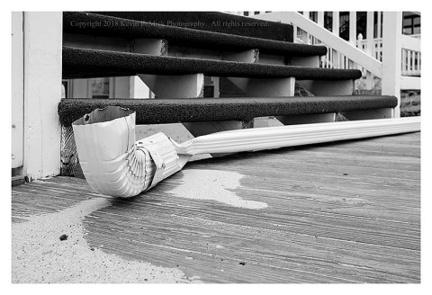 BW photograph of a downed water spout and gutter on the boardwalk in Ocean City.