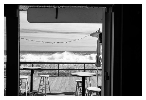BW photograph of the surf looking out of the door of the Turtle Bay Cafe.