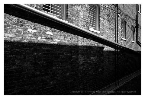 BW photograph of a wall with a diagonal downspout in contrasty light.